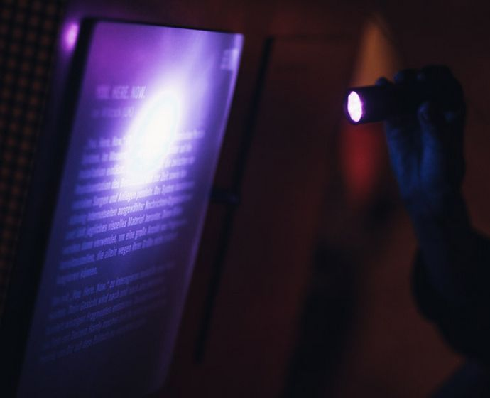 Visitor uses flash light to look at display item